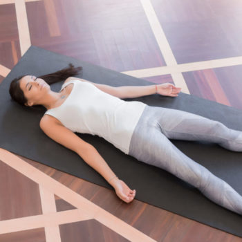 Top view Young woman meditating on a wooden floor and lying in Shavasana pose. View from above of attractive yogi working out, doing yoga exercise on black mat. Lifestyle